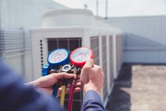 Technician is checking air conditioner ,measuring equipment for filling air conditioners royalty free stock photo