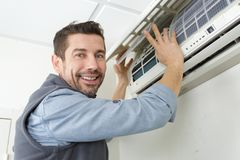 Air conditioning technician preparing to install new air conditioner royalty free stock photography