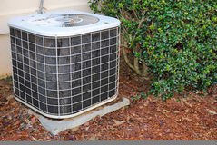Air conditioning Unit. Residential air condition unit in mulch near a home Stock Photos