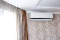 Air conditioning on the wall inside the room in apartment, switched off. Interior in calm beige tones royalty free stock image