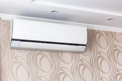 Air conditioning on the wall inside the room in apartment, switched off. Interior in calm beige tones. Close-up stock image