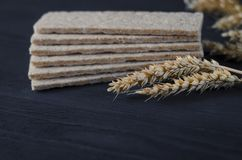 Air dietetic loaves lie on a wooden table on a dark background next to the ears of wheat royalty free stock photos