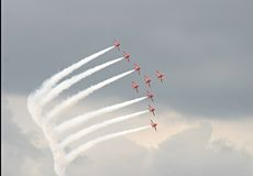 Air display 1. Red military jets flying in formation display against ominous cloudy background Stock Images