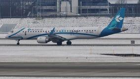 Air Dolomiti делая такси на снежном взлётно-посадочная дорожка, авиапорте Мюнхена