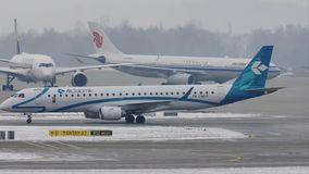 Air Dolomiti Embraer ERJ-195 I-ADJT in Munich Airport, winter. Air Dolomiti plane taxiing on Munich Airport MUC, Germany stock footage