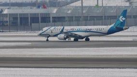 Air Dolomiti que hace el taxi en la pista nevosa, aeropuerto de Munich