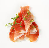 Air dried ham with thyme. Slices of air dried ham with thyme on white background Stock Image