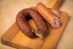 Air dried pork sausage ring and German Bierbeißer are two sorts of Salami on wooden board stock image
