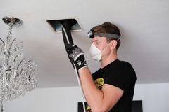 Air duct cleaning, drill, ductwork, man, hvac. Air duct cleaning with drill, cleaning the registers, white man royalty free stock photo