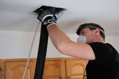 Air duct cleaning, drill, ductwork, man, hvac. Air duct cleaning with drill, cleaning the registers, white man royalty free stock images