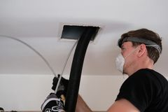 Air duct cleaning, drill, ductwork, man, hvac. Air duct cleaning with drill, cleaning the registers, white man stock photos