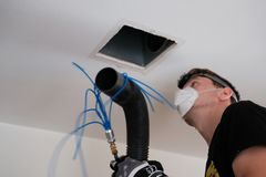 Air duct cleaning, drill, ductwork, man, hvac. Air duct cleaning with drill, cleaning the registers, white man royalty free stock image