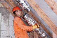 Air duct installation. Worker in the attic connects metal air ducts royalty free stock photos