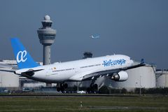 Air Europa Express Embraer jet taking off from Amsterdam Airport AMS. Schiphol. ATC Air traffic control tower stock image