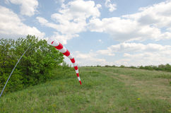 Air field direction sign and a wind force windsock against the  blue sky with clouds.  Stock Photo