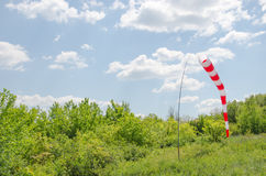 Air field direction sign and a wind force windsock against the  blue sky with clouds.  Royalty Free Stock Image