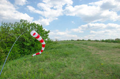 Air field direction sign and a wind force windsock against the  blue sky with clouds.  Royalty Free Stock Images