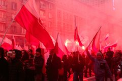 Independence Day March in Warsaw Poland Marred by Violence and Controversy. The air is filled red with the smoke of flares as protesters wave large and small Stock Photo