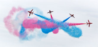 Air Force stunt team. Red Arrows stunt team breaking up formation with colored smoke Stock Photos