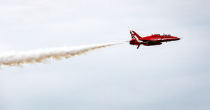 Air Force stunt team soloflight. Red Arrows stunt teamjet flying solo with white smoke trail Royalty Free Stock Image