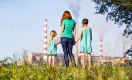 air framtid för omsorgslampglasbegreppet henne ungar som ser unga förorena stjälkar för modern Royaltyfri Bild