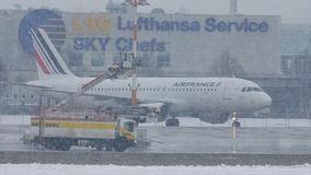 Air France on heavy snow, Munich Airport. Air France aircraft doing taxi on Munich Airport, snow on runway. Lufthansa Service building on background stock footage