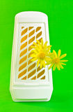 Air freshener. A closeup of a WC air freshener and yellow flowers Stock Photography