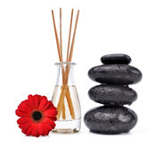 Air freshener with wooden aroma sticks and black spa stones. On white background Royalty Free Stock Images