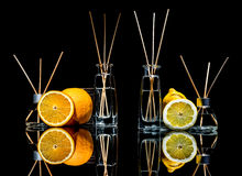 Air fresheners in a glass jars with sticks and lemon, green apple and orange with reflection isolated on a black background. Stock Photo