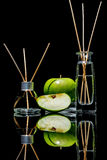 Air fresheners with green apple scent in a beautiful glass jars with sticks and whole green apple and a slice of apple Stock Photography