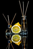 Air fresheners with lemon scent in a beautiful glass jars with sticks and whole lemon and a slice of lemon with reflection. Isolated on a black background Royalty Free Stock Photography