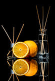 Air fresheners with orange fruits scent in a beautiful glass jars with sticks and whole orange and a slice of orange. With reflection isolated on a black Royalty Free Stock Photos