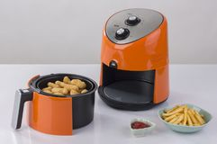 Air fryer machine. With chicken and french fried stock images