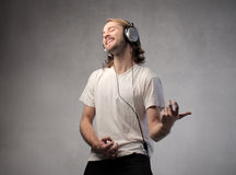 Air guitar. Smiling young man listening to music and playing air guitar Stock Photos