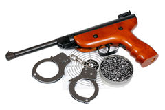 Air gun with gun-shield, pellets in box and handcuffs Royalty Free Stock Photos