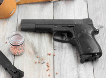 Air gun, holder, holster and balls for firing on a wooden table. Royalty Free Stock Image