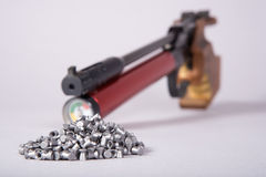 Air gun with pellets. Sport air gun with piles of pellets(focus on piles of pellets Royalty Free Stock Photo
