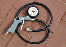 Air gun with pressure gauge. And connecting hose for pumping tires on the background paving slabs Royalty Free Stock Photo