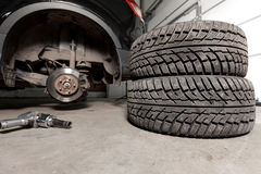 Air gun to tighten a tire bolts on a suspended car at an auto shop.  Royalty Free Stock Photography