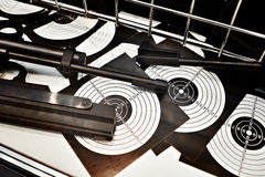 Air guns and target on table in shooting range Royalty Free Stock Images