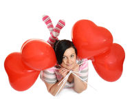 Air hearts. The young woman lays and holds balls Royalty Free Stock Photo