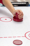 Air hockey. Hand on a mallet over air hockey table Royalty Free Stock Photography