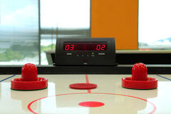Air Hockey Game. Air hockey table with paddle, puck and scoreboard showing scores royalty free stock photography
