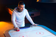 Air hockey game is fun even for adults. Playing a game of air hockey in the game room Stock Photos