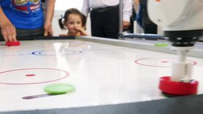 Air hockey table and person`s hand playing with white robot arm. Media. Different working robots collection presented on stock footage