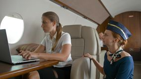 Air hostes asking businesswoman about service inside of luxury business plane. Business lady working at laptop and surfing in internet while aircraft flying stock footage