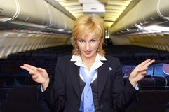 Air hostess gesturing. In the empty airliner cabin Stock Images
