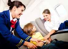 Air hostess helping a kid Royalty Free Stock Image