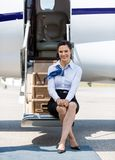 Air Hostess Sitting On Ladder Of Private Jet Stock Photo