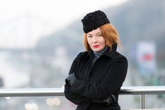 Air-hostess winter dress code. Woman standing near of bridge barrier in black coat. Portrait of lady with red hair crossing hands. Portrait of air-hostess Royalty Free Stock Photography